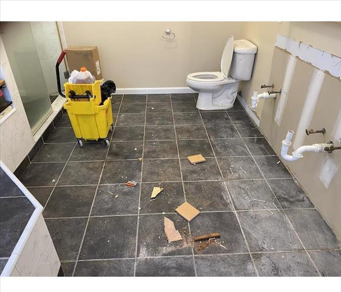 Bathroom with debris on the tile floor bare wall