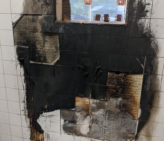 Commercial fire damage on restaurant kitchen tile wall