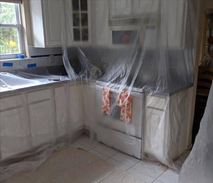 Kitchen with white wood cabinets with taped up plastic barriers for protection